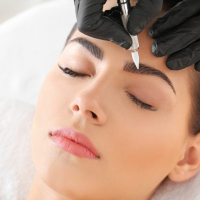 Young woman undergoing procedure of eyebrow permanent makeup in beauty salon